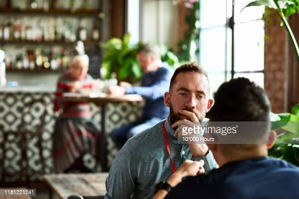 man listening thoughtfully to business colleague in restaurant - serious stock pictures, royalty-free photos & images