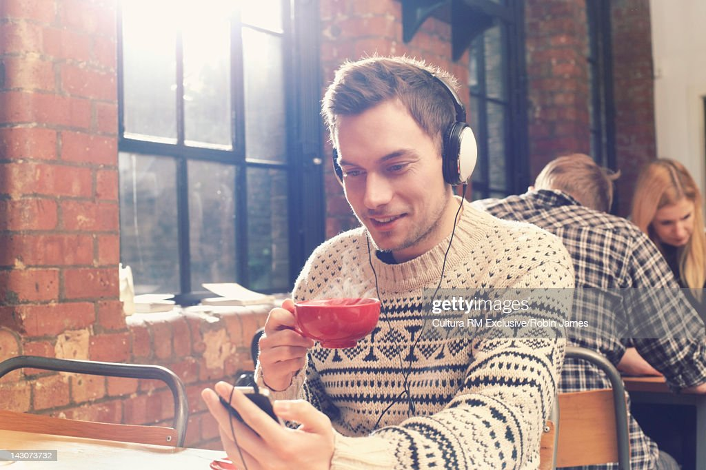 Man listening to headphones in cafe : Stock Photo