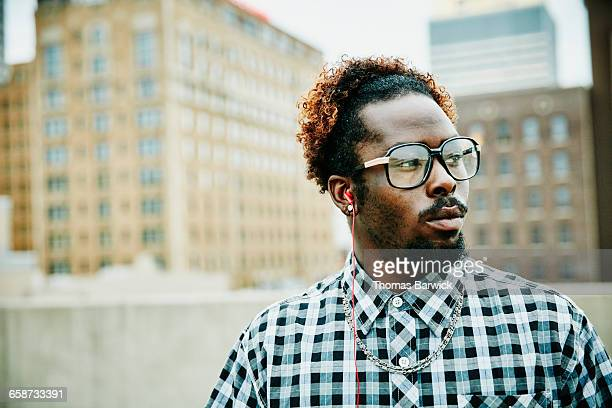 Man listening to headphones on rooftop