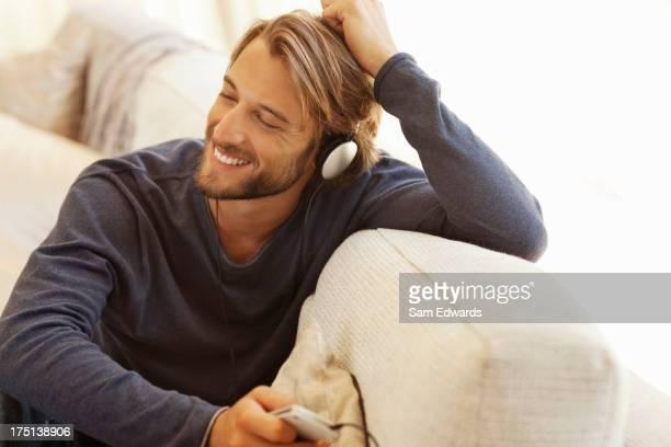Mann Kopfhörer hören auf sofa