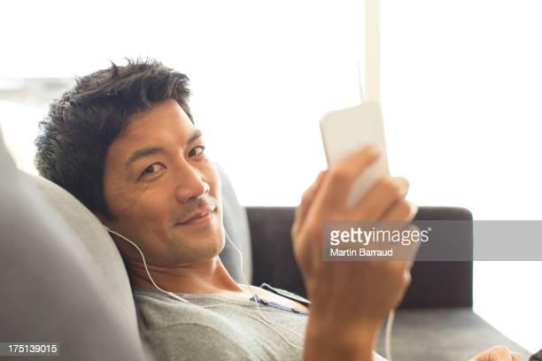 Man listening to headphones on sofa