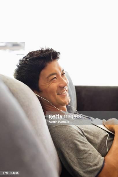 男性に耳を傾けるのヘッドフォンのソファー