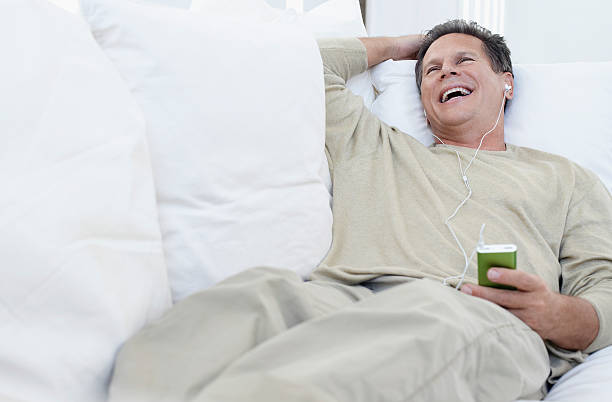 Man Listening to mp3 player on Sofa