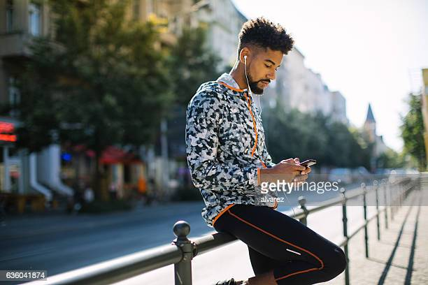 Man listening to music after jogging in city