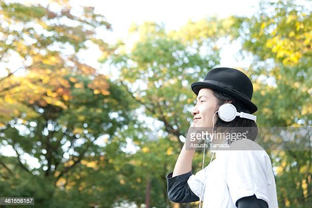 Man listening to music among trees,smiling