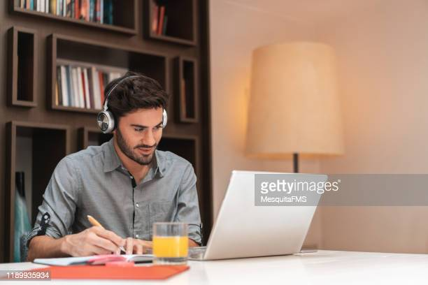 man listening to music and surfing the internet - mid adult stock pictures, royalty-free photos & images