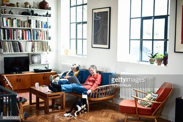 man listening to music and woman stroking cat - 69 position stock photos and pictures
