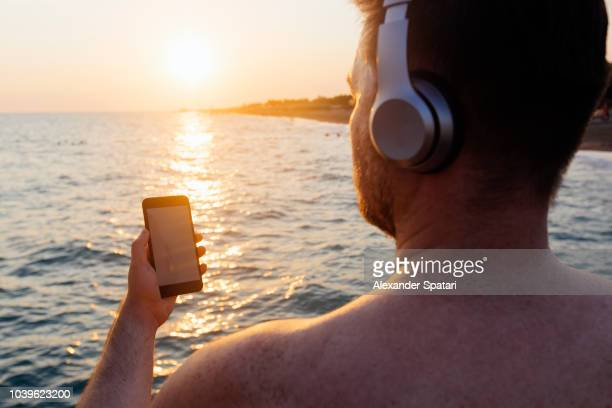 Man listening to music from his smart phone using bluetooth earphones, looking at sea during sunset