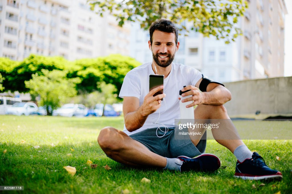 Man listening to music in the park and resting : Stock Photo