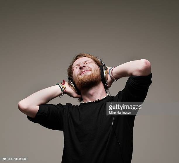 Man listening to music on headphones with head in hands