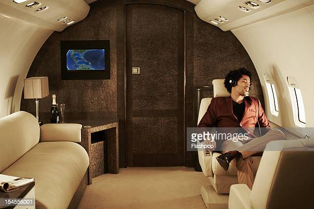 man listening to music on private jet - vehicle interior stock pictures, royalty-free photos & images