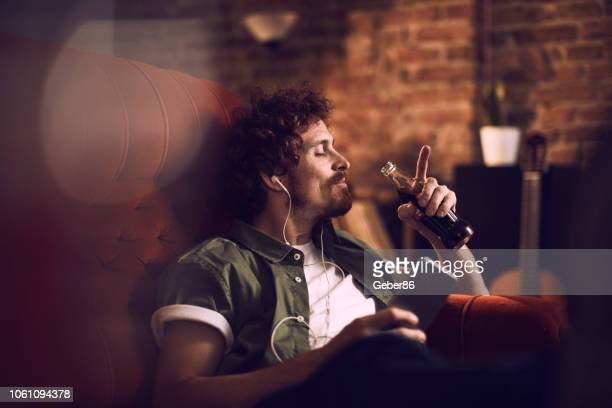 man listening to music - man cave stock pictures, royalty-free photos & images