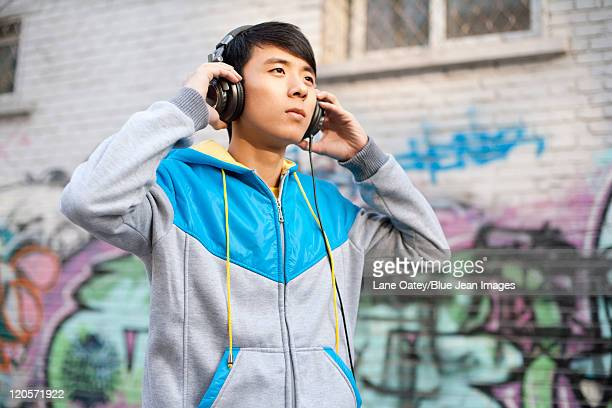 man listening to music - hoodie headphones stock pictures, royalty-free photos & images