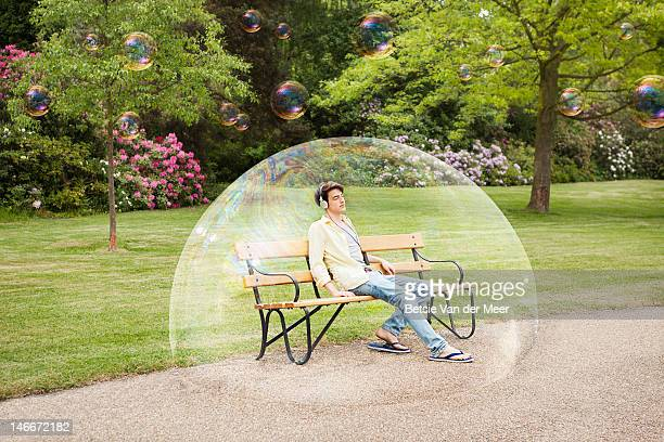 man listening to music sitting in bubble. - protection stock pictures, royalty-free photos & images