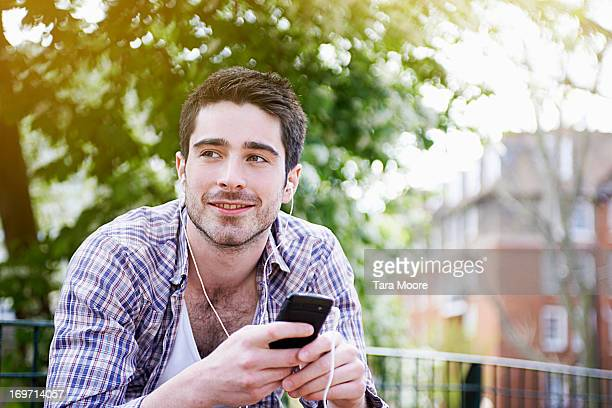 man listening to music with earphones and mobile