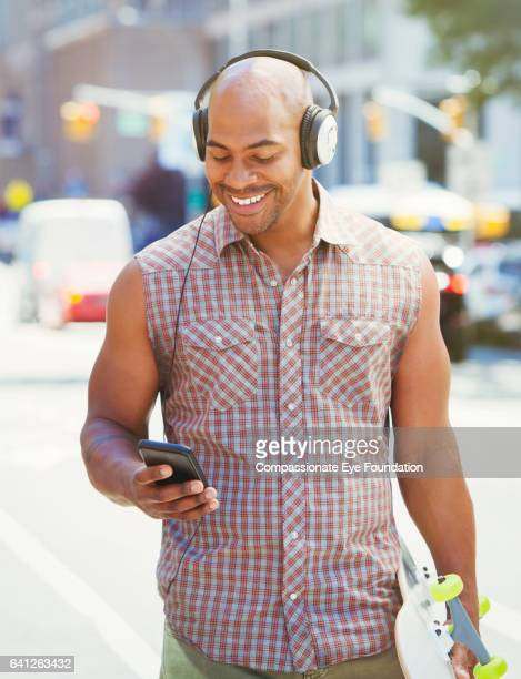 Man listening to music with headphones and cell phone in city street