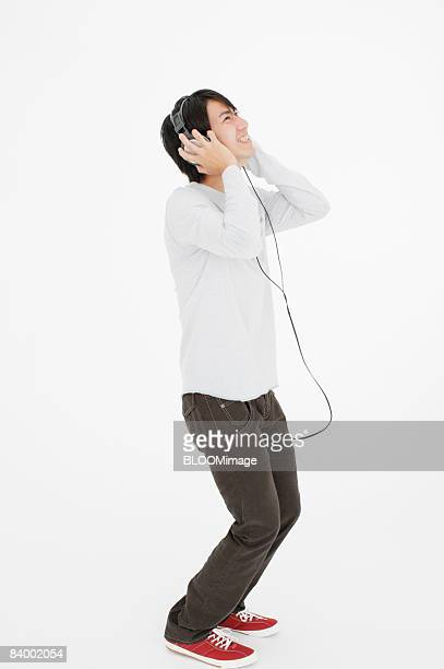 Man listening to music with headphones, studio shot