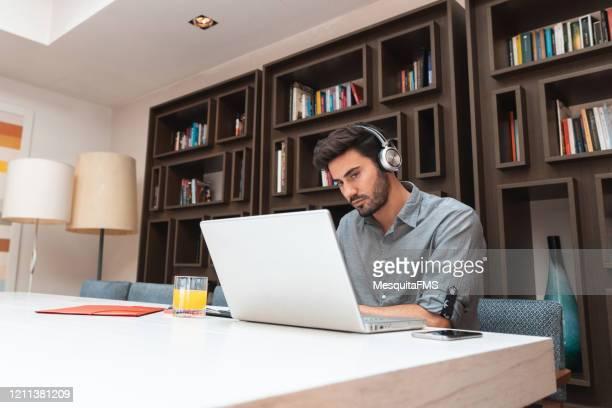 man listening to news at the library - sentar se imagens e fotografias de stock