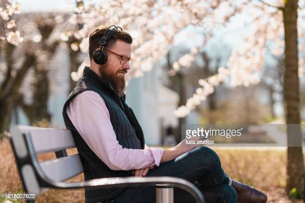 man listening to podcasts on his smart phone - listening stock pictures, royalty-free photos & images
