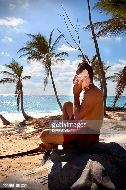 Man listening to shell at beach, side view
