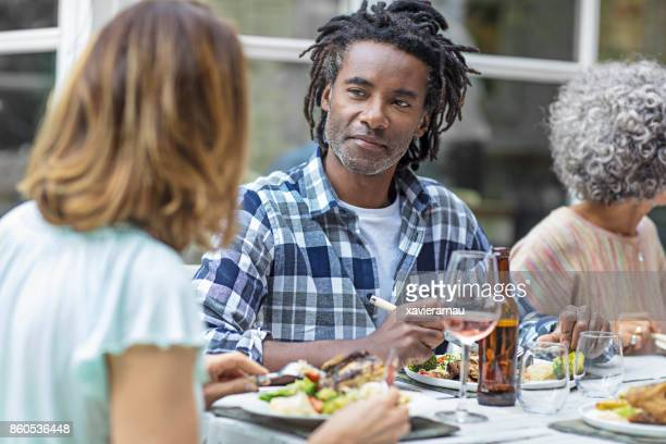 Man listening to woman while having food in yard