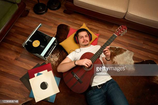 man listening vinyl records and playing guitar on the floor - modern rock stock pictures, royalty-free photos & images