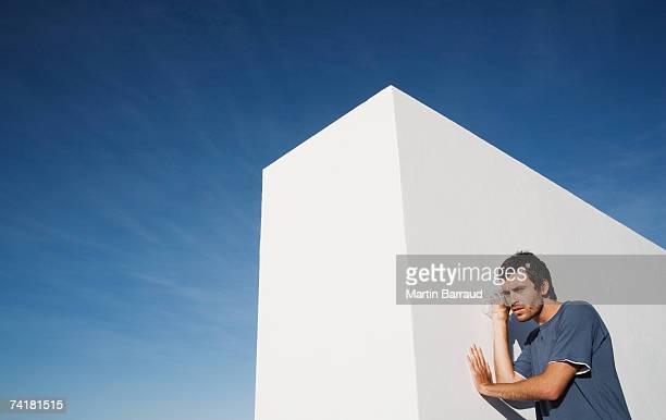 Homme écoute à travers le Mur avec verre en plein air