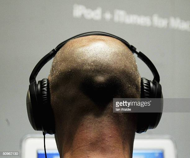 A man listens to music from an iPod at the launch of Apple's iTunes Music Store in the territories of Great Britain Germany and France on June 15...