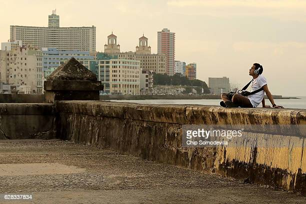 A man listens to music while sitting on the seawall along the famous Malecon as daily life resumes in the capital city following a nineday mouring...