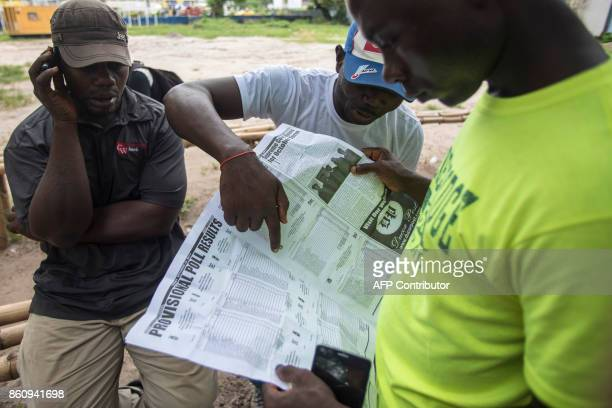 A man listens to the radio next to two men reading the newspaper in order to find provisionals elections results in Monrovia on October 13 2017...