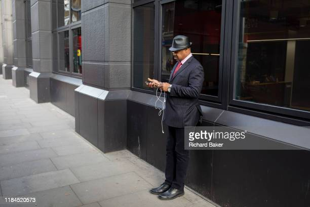 A man listens via headphones at a bus stop on Farringdon Road on 20th November 2019 in the City of London England