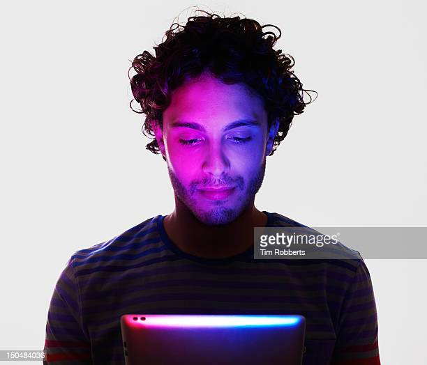 man lit by digital tablet - one man only stock pictures, royalty-free photos & images