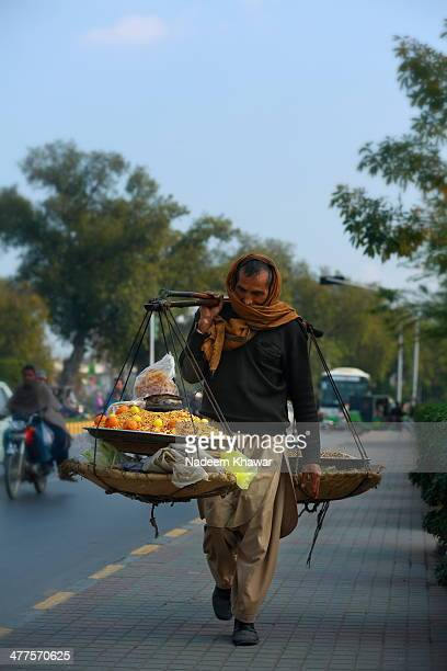 "Man loaded with salty ""Dal Chana"" which are served hot and with lemon, on The Mall Road Lahore in search of customers. This traditional butt..."