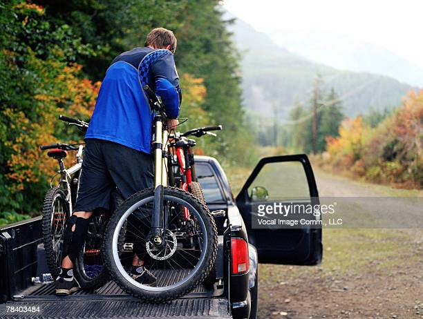 Man loading bikes on pickup truck