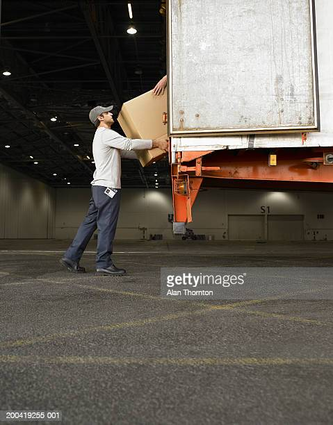 Man loading box into truck, side view