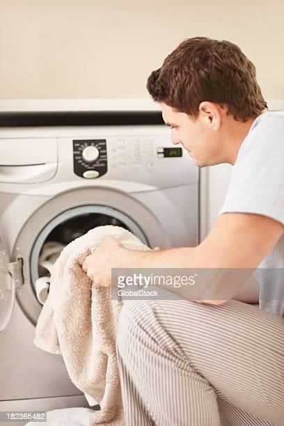 Mann Beladen Kleidung in der Waschmaschine