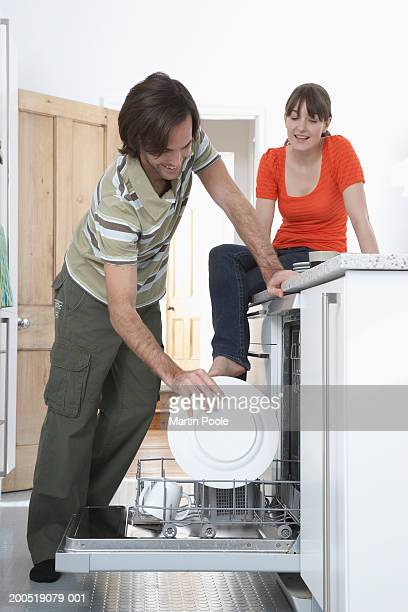 Man loading dishwasher, woman sitting on kitchen counter, smiling