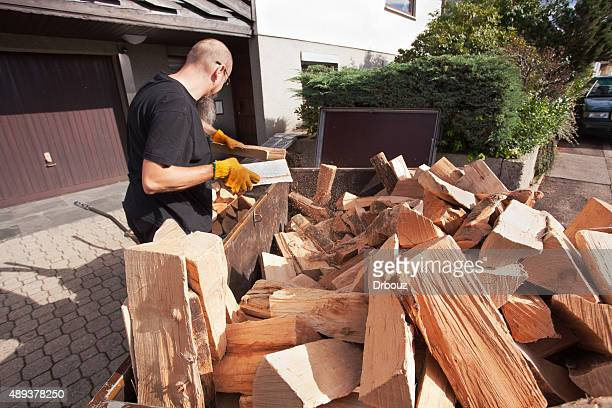 Man loading hand wagon with firewood