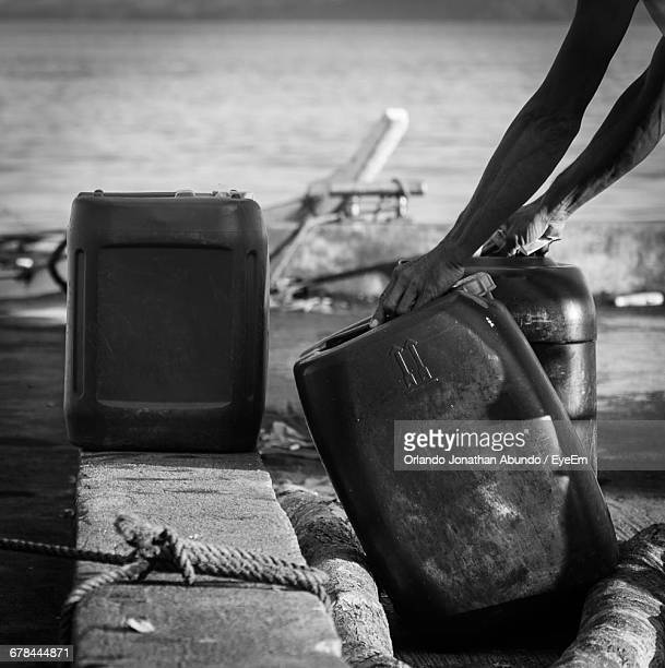 Man Loading Heavy Gallon Of Fuel Can On River Bank