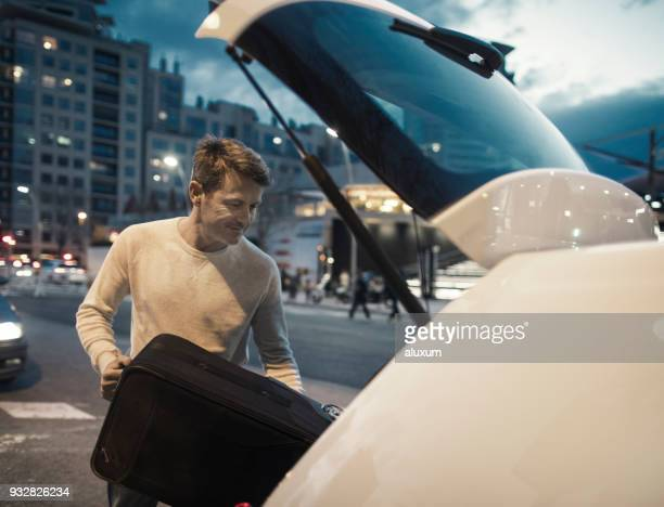 man loading luggage in car trunk - car trunk stock pictures, royalty-free photos & images