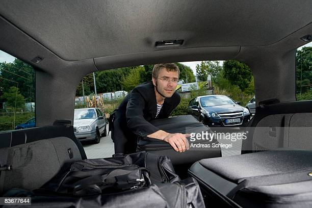 A man loading luggage into the boot of a car