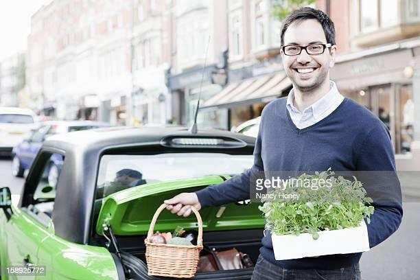 Man loading produce into car