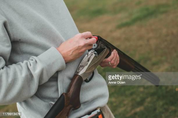 man loading shotgun shells into a gun - shotgun stock pictures, royalty-free photos & images