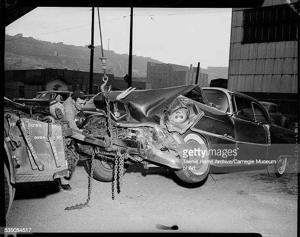 Man loading wrecked Cadillac car belonging to Walt Harper onto tow truck Pittsburgh Pennsylvania November 1956
