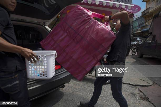 A man loads a shopping bag into the trunk of a car in the Chinatown area of Bangkok Thailand on Saturday Oct 21 2017 Thaihousehold consumption worth...