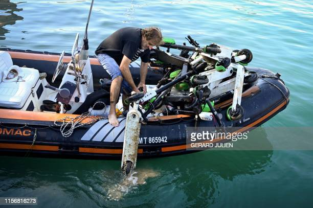 TOPSHOT A man loads an escooter onto an inflatable boat as volunteer divers recover them from the seawater along the Marseille's coast southeastern...