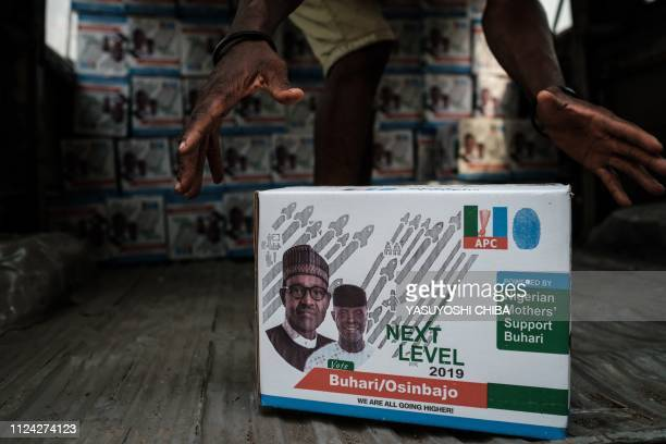 Man loads boxes of food donation bearing the faces of Nigeria's incumbent President Mohammadu Buhari and Vice President Yemi Osinbajo onto a van in...