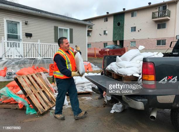 A man loads sandbags into a pickup truck in preparation for increased flooding in Gatineau Quebec on April 24 2019 Flooding in eastern Canada forced...