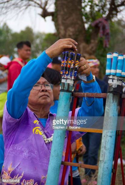A man loads small rockets for launch as a gesture to god for the sake of the rainy season during the Ban Bung Fai Rocket Festival in Yasothon Thailand