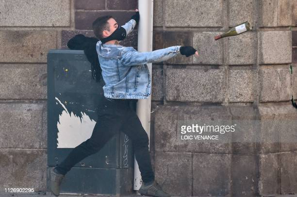 A man lobs a glass bottle as members of the yellow vest take part in the 15th consecutive Saturday of demonstrations in Rennes western France on...